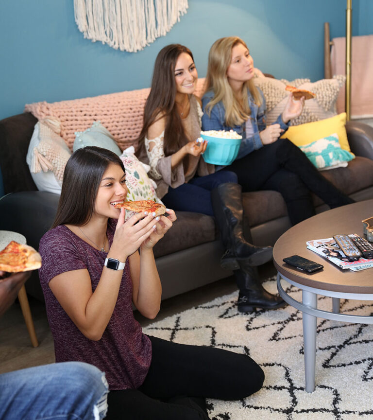 A group of young residents eating pizza in their living room